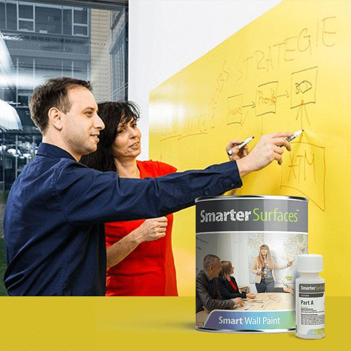 Two people writing on a yellow smarter surfaces writable wall