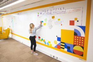 woman-using-whiteboard-wall